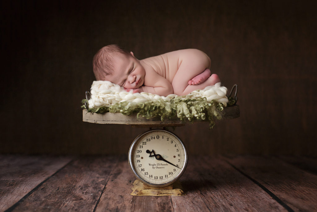 Baby boy on scale for newborn portraits.