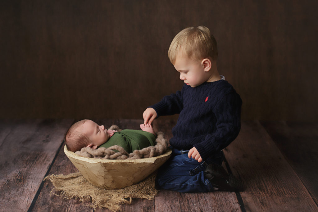 Brother touches his new baby brother